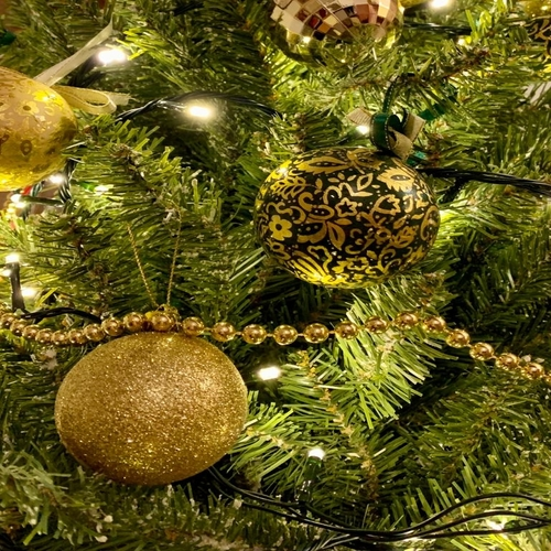Christmas tree decorated with baubles and lights in the lounge ready for your presents at a Bramble Cottage Christmas.